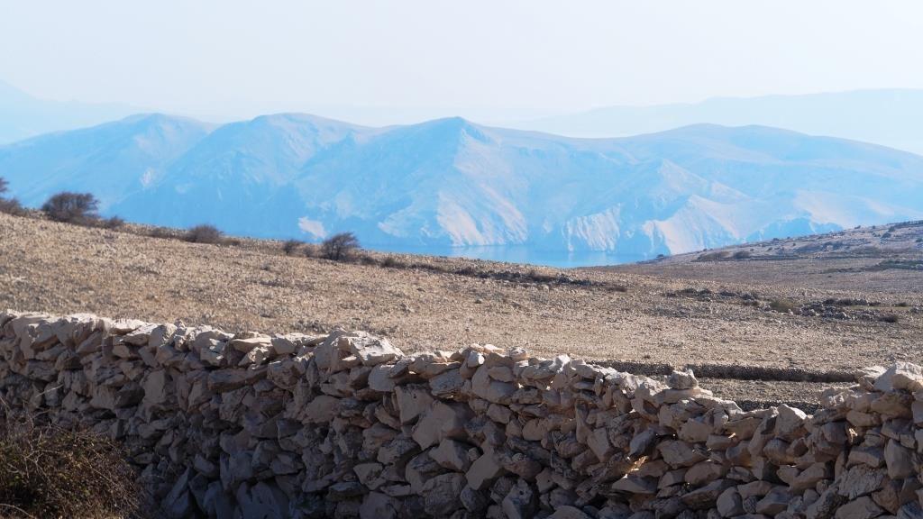 Pogled s bašćanskog platoa na otoku Krku na litice susjednog otočića Prvića, ornitološkog rezervata u kojem se također gnijezde supovi.